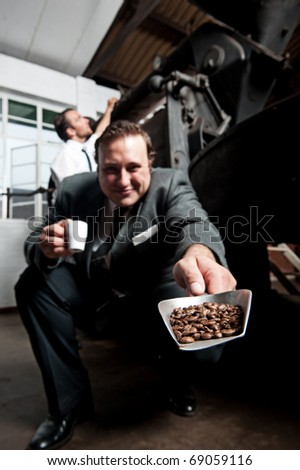 Man in suit showing freshly roasted coffee beans - stock photo