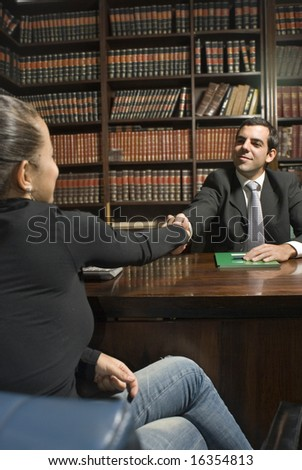 Man in suit sits behind desk. He shakes hand of woman on other side. Vertically framed photo. - stock photo