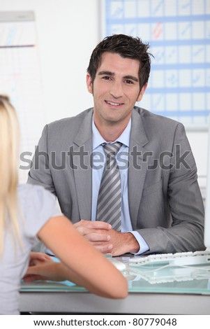 Man in suit sitting across a desk from a young woman with a schedule in the background - stock photo