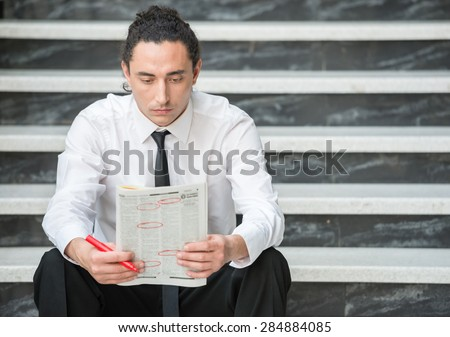 Man in suit sitting at stairs with  newspaper and searching job.