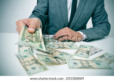 man in suit sitting in a desk full of dollar bills offering one of them to the observer - stock photo