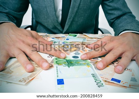 man in suit sitting in a desk full of euro bills trying to hold them depicting wealth or greediness - stock photo