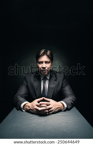 Man in suit sitting in dark room illuminated only by some light and looking in camera - stock photo