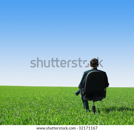 Man in suit sitting on chair in green field - stock photo