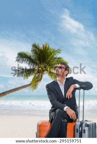 Man in suit sitting on his luggage at the tropical beach