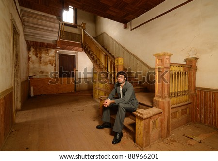 Man in suit sitting on the stairs of an old abandoned house.