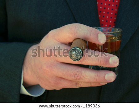 man in suit smoking a cigar and holding a shot of whiskey