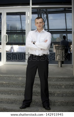 Man in suit standing in front of a building. Background is out of focus.