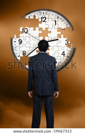 man in suit standing in front of a clock puzzle with missing pieces - stock photo