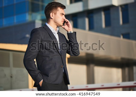 Man in suit talking on mobile phone on background of building