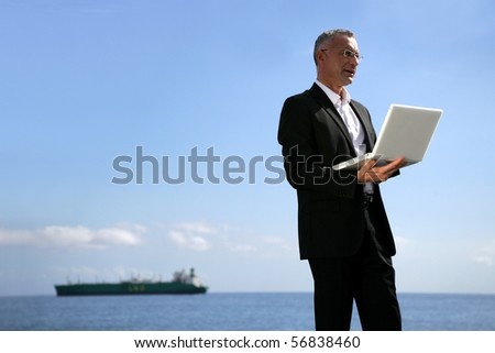 Man in suit with a laptop computer - stock photo