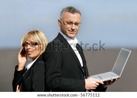 Man in suit with a laptop computer back to back with a woman in suit phoning