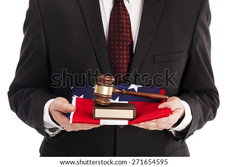 Man in suit with american flag and gavel - stock photo