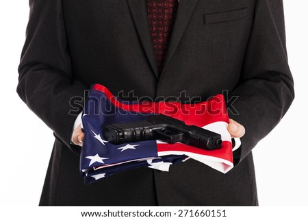 Man in suit with american flag and gun on a white background - stock photo