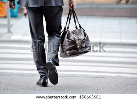 Man in suit with bag, on zebra crossing - stock photo