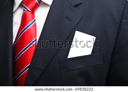 Man in suit with blank card in his pocket - stock photo