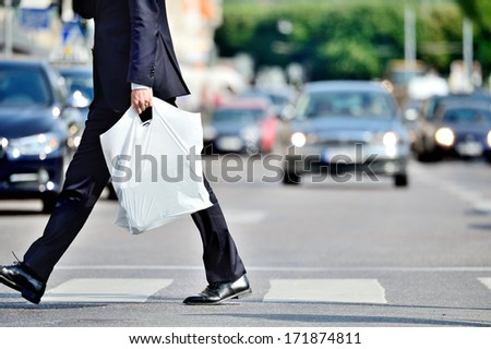 Man in suit with plastic bag crossing street - stock photo