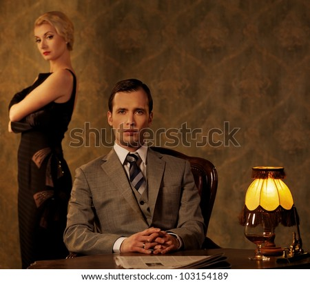 Man in suit  with woman behind him. - stock photo
