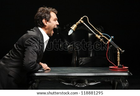 man in suit yelling at a lamp, isolated on a black background.
