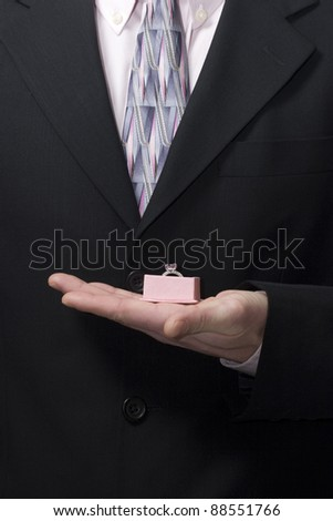 man in suite holds costume jewel in hand - stock photo