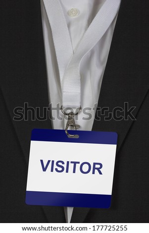 man in suite wearing a Visitors pass arround his neck - stock photo