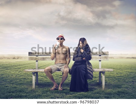 Man in summer clothes sitting on a park bench with woman wrapped in warm clothes beside him - stock photo