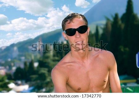 Man in sun glasses posing against beautiful summer background - stock photo