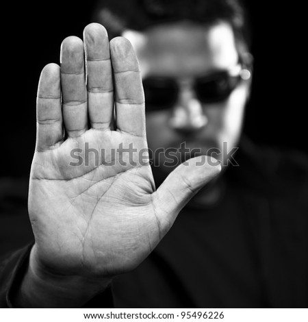 Man in sunglasses gesturing to stop