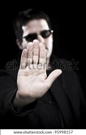 Man in sunglasses holds up hand - stock photo