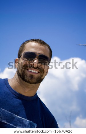 Man in sunglasses smiling into camera - stock photo