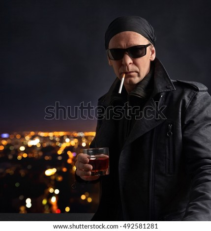 man in sunglasses with a glass of whiskey on the background of night city
