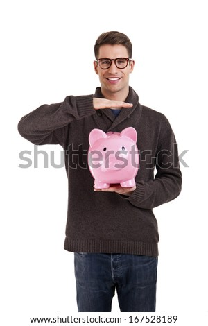 Man in sweater protect piggy bank against white background - stock photo