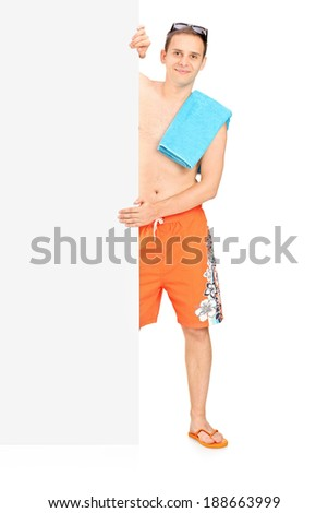 Man in swimsuit standing behind black panel isolated on white background - stock photo