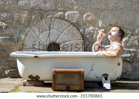 man in the bathtub smoking a pipe and listening to radio - stock photo