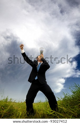man in the black suit and holding megaphone shouting to the storm - stock photo