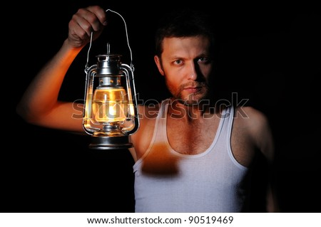 Man in the dark with a kerosene lamp on black background, concept carrying light - stock photo