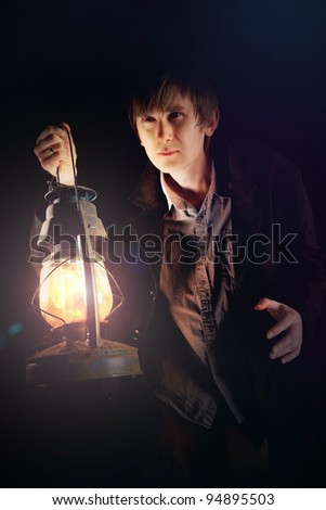 Man in the dark with lantern in his hand