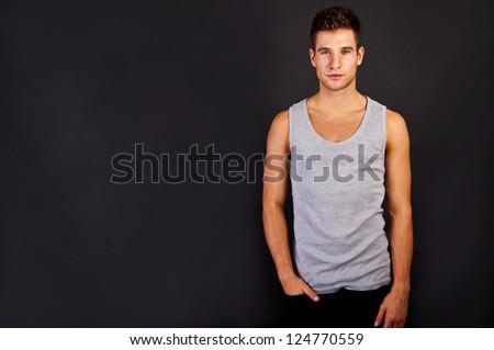 Man in the grey tank top shirt look at the camera - stock photo