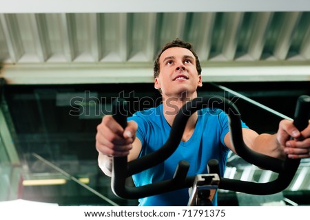 Man in the gym, exercising his legs doing cardio training on bicycle - stock photo