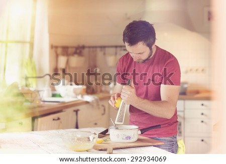 Man in the kitchen grating lemon zest into a creamy sauce - stock photo