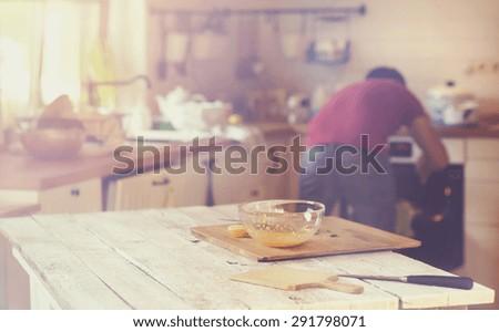 Man in the kitchen preparing a sauce for a salmon tagliatelle. - stock photo