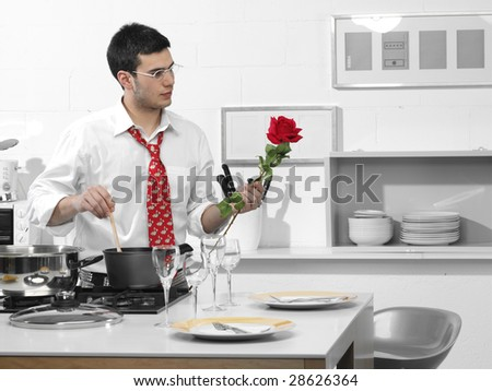 man in the kitchen waiting for his girlfriend with a rose in hand - stock photo