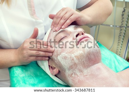 man in the mask cosmetic procedure in spa salon - stock photo