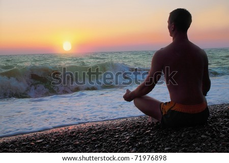 Man in the meditation on the shore of the sea