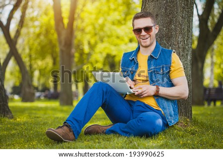 man in the park sitting on the grass with a laptop