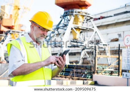 man in the port works on the tablet - stock photo