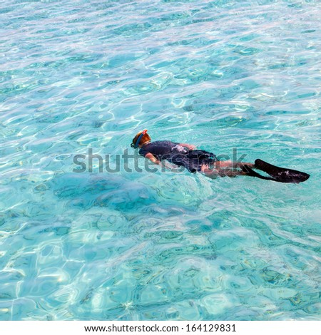 man in the sea with the equipment for a snorkeling - stock photo
