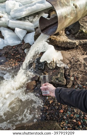 Man in the spring sunny day stands with empty glass in his hand near sewer from which water flows into the river - stock photo