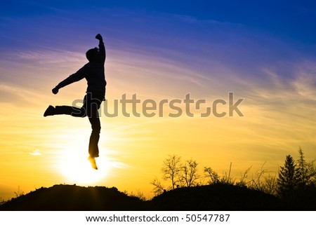 Man in the sunset, happy and jumps.