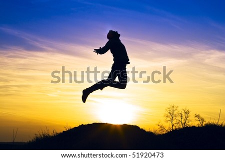 Man in the sunset jump and shout.